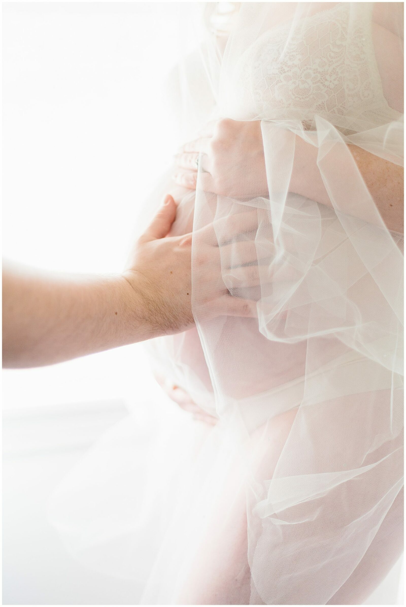 soft colors, maternity portrait of mother standing with lace, father's hand on belly